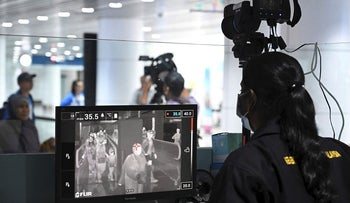A Malaysian health officer screens arriving passengers with a thermal scanner at Kuala Lumpur International Airport in Sepang on January 21, 2020 as authorities increased measure against coronavirus