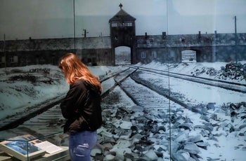 A visitor looking at an exhibition in front of a picture of the Auschwitz death camp in Nazi-occupied Poland, at the Yad Vashem Holocaust memorial center in Jerusalem, January 20, 2020.