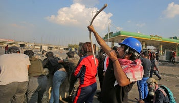 An Iraqi protester uses a makeshift bow and arrow amid clashes with riot police following a demonstration at Baghdad's Tayaran Square, east of Tahrir Square, January 20, 2020.
