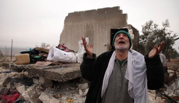 A Syrian man gestures as he stands next to the rubble of the house where he lived with his displaced family in the village of Kafr Taal, January 20, 2020.