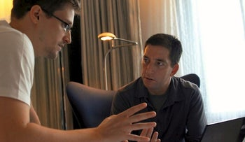 """In this image released by Radius TWC, Edward Snowden, left, appears with Glenn Greenwald in a scene from """"Citizenfour,"""" a documentary that intimately captures  Snowden during his leak of NSA documents"""