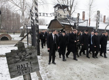 "Poland's then-President Bronislaw Komorowski, second right, pass under the German inscription ""Arbeit Macht Frei"" (Work will Set You Free) at the former German Nazi death camp of Auschwitz during the 70th anniversary of the death camp's liberation on January 27, 2015"