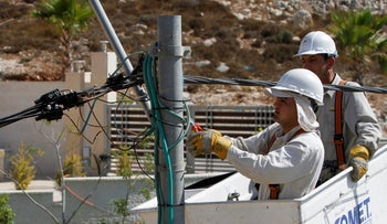 Electricians install new power transmission lines at a construction site in the West Bank city of Ramallah, 2015.