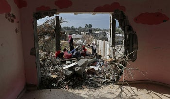 Members of a Palestinian family are seen at the ruins of their destroyed house, on a winter cold day in the southern Gaza Strip January 13, 2020.
