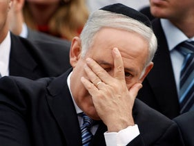 Israeli Prime Minister Benjamin Netanyahu covers his face during a ceremony marking the annual Holocaust Remembrance Day at the Yad Vashem Holocaust Memorial in Jerusalem. April 12, 2010