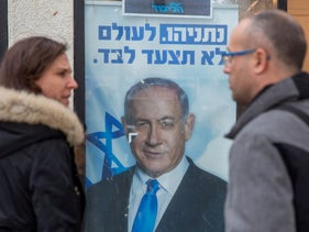 People look at a poster of Israel Prime Minister and governing Likud party leader Benjamin Netanyahu at a voting center in the northern Israeli city of Hadera, Thursday, December 26, 2019.