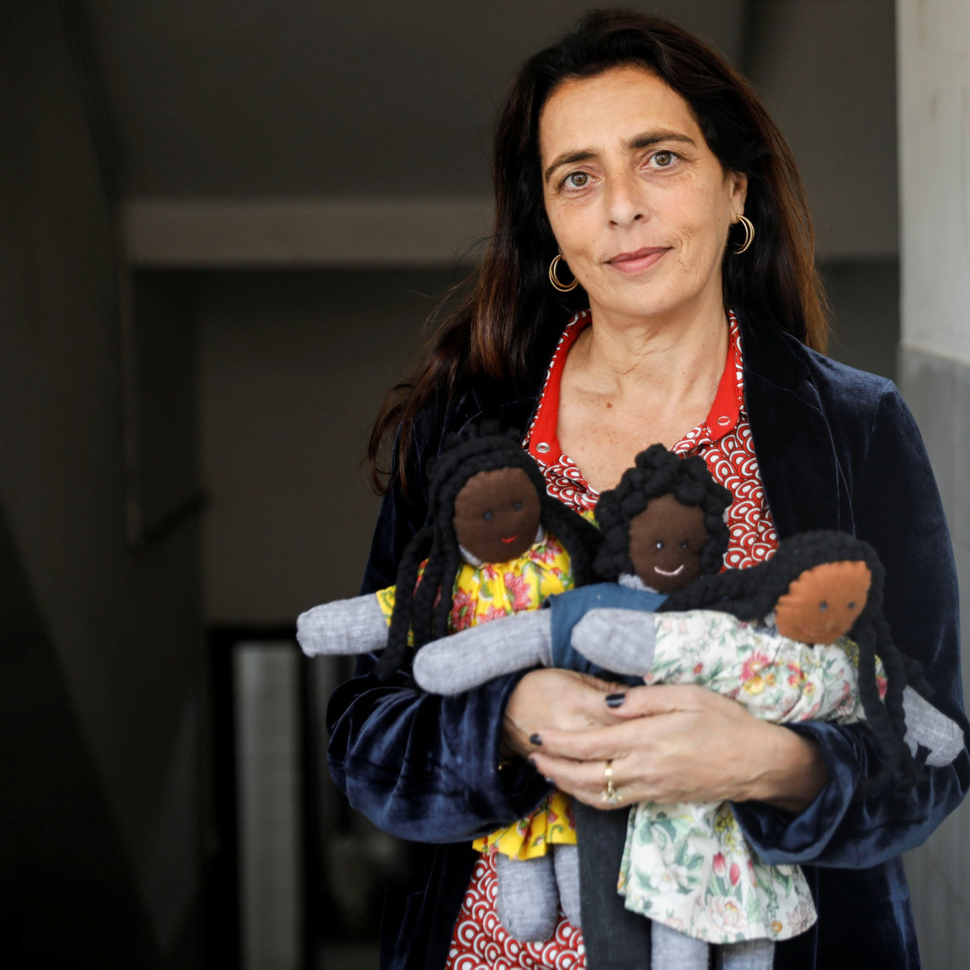 Mymin Kahn, the founder of the project, with the dolls they prepared by asylum seekers.