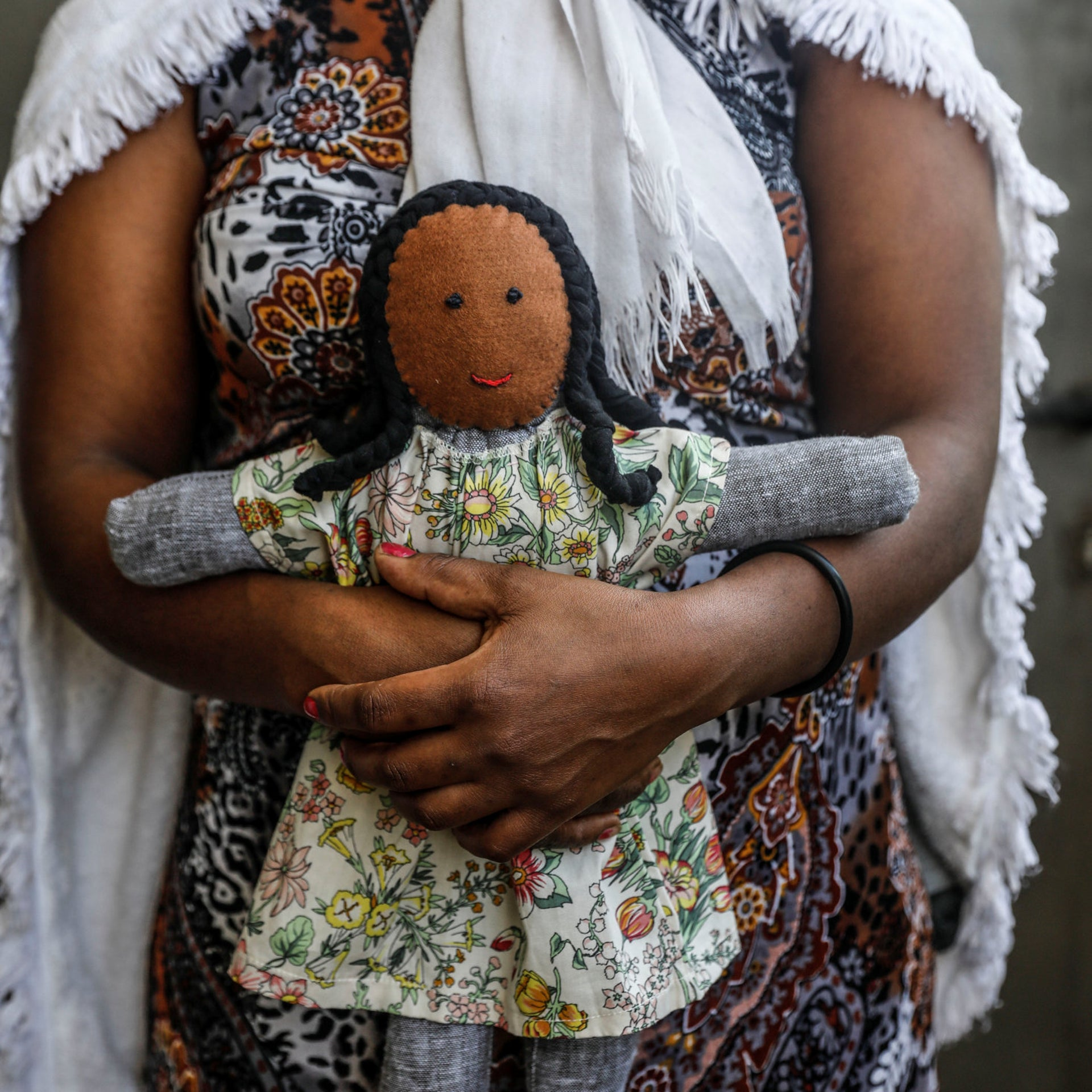 An asylum seeker presents one of the dolls she made.