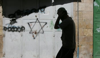 An Israeli settler walks past a Star of David graffiti on the door of a closed Palestinian shop in the Jewish settlement area of the divided West Bank city of Hebron on January 8, 2010