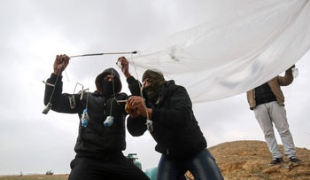 Young Palestinian men prepare a flammable object to be flown toward Israel, near the Israel-Gaza border east of Rafah in the southern Gaza Strip, January 18, 2020.