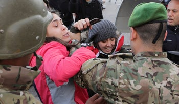 Army soldiers scuffle with anti-government protesters blocking a road leading to the parliament building in downtown Beirut, Lebanon, Monday, Jan. 27, 2020.