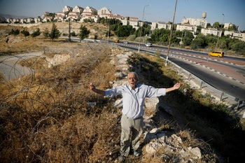 Palestinian Ali Farun, 74, gestures by a road in al-Eizariya town with the Jewish settlement of Maale Adumim in the background, in the Israeli-occupied West Bank, July 27, 2019