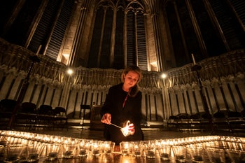 York Minster's Leanne Woodhurst helps light some of the 600 candles in the shape of the Star of David, in memory of more than 6 million Jews murdered by the Nazi. Chapter House, York Minster, Jan. 23, 2020
