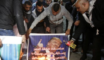 Palestinians in the Deheisheh refugee camp on the West Bank prepare to burn a picture of Trump.