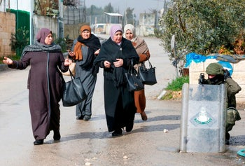Palestinian women walk past an Israeli soldier during clashes with protesters following a demonstration in al-Aroub Palestinian refugee camp, January 29, 2020.