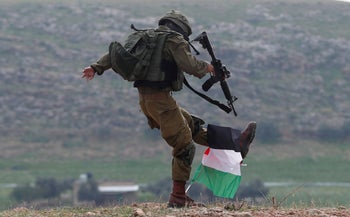 An Israeli soldier kicks a Palestinian flag during a protest against the U.S. president Donald Trump's Middle East peace plan, in Jordan Valley in the Israeli-occupied West Bank, January 29, 2020.