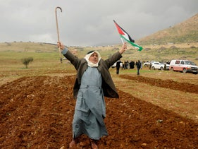 A demonstrator holds up a cane and a Palestinian flag during a protest against the U.S. president Donald Trump's Middle East peace plan, in Jordan Valley in the West Bank, January 29, 2020.