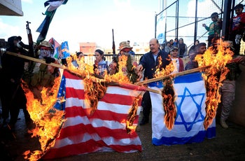 Demonstrators set fire to an Israeli and U.S. flag during a protest against U.S. President Donald Trump's Middle East peace plan, Ain al-Hilweh Palestinian refugee camp, near Sidon, Lebanon, January 29, 2020.