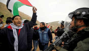 A demonstrator holds a Palestinian flag in front of Israeli forces during a protest against the U.S. president Donald Trump?s Middle East peace plan, in Jordan Valley in the Israeli-occupied 0