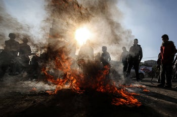 Palestinian demonstrators burn tyres during a demonstration against a US brokered Middle East peace plan, in Rafah in the southern Gaza Strip, on January 29, 2020
