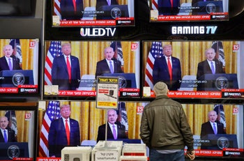 An Israeli man watches the televised press conference of US President Donald Trump and Israeli Prime Minister Benjamin Netanyahu at an electronics shop in the Israeli city of Modiin on January 28, 2020
