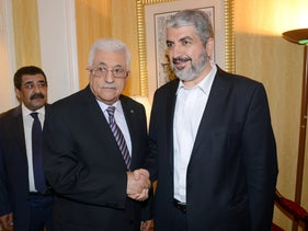 Palestinian president Mahmoud Abbas (L) shakes hands with then Hamas chief Khaled Meshaal in Doha, Qatar, May 5, 2014