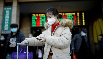 A woman wearing a face mask uses her cellphone as she walks outside Beijing Railway Station as the country is hit by an outbreak of the new coronavirus, in Beijing, China January 30, 2020.