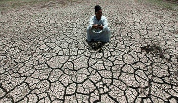 An Egyptian farmer squats down on cracked soil to show the dryness of the land due to drought in a farm formerly irrigated by the river Nile on June 4, 2013.