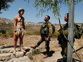 A Jewish settler and IDF soldiers near the Anar Springs in the West Bank, January 2020.