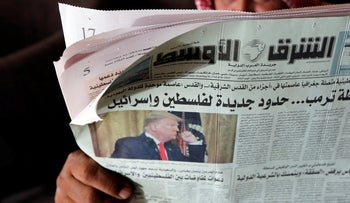 A man holds the daily Asharq Al-Awsat newspaper fronted by a picture of President Donald Trump, at a coffee shop in Jiddah, Saudi Arabia, Jan. 29, 2020. U.S.