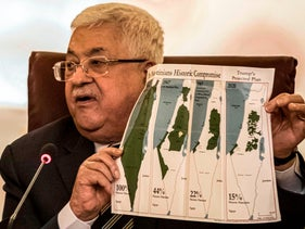 Mahmoud Abbas holds a placard showing maps of Palestine at an Arab League emergency meeting, Cairo, February 1, 2020