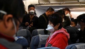 Passengers wear protective face masks as they wait to disembark from an Air China flight from Melbourne, in Beijing on February 1, 2020.