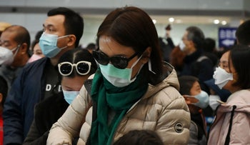 A woman wears a protective face mask and gloves while waiting to go through immigration at Beijing airport on February 1, 2020