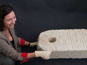 Shirly Ben-Dor Evian, curator of Egyptian archaeology at the Israel Museum, with the ancient Egyptian anchor found off Atlit
