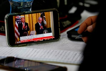 Members of the media watch the televised press conference of US President Donald Trump and Israeli Prime Minister Benjamin Netanyahu in the West Bank city of Ramallah on January 28, 2020