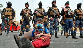 Anti-government protesters stage a sit-in while security forces stand guard during ongoing protests in downtown Baghdad, Iraq, Jan. 19, 2020.
