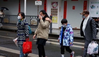 People wearing face masks cross a street in Jiujiang, Jiangxi province, China, as the country is hit by an outbreak of the novel coronavirus, February 2, 2020.