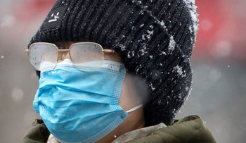 A woman's eyeglasses are fogged up as she wears a face mask during a snowfall in Beijing.
