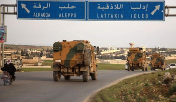 Turkish military vehicles drive in a convoy headed for the south of Idlib province as they pass by the town of Atareb in the western countryside of Aleppo, February 3, 2020.