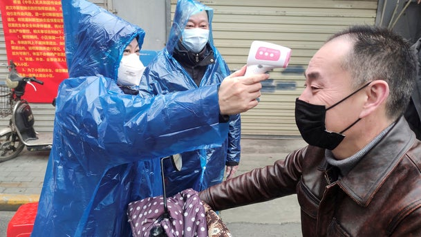 A man is checked for fever amid the coronavirus outbreak in Wuhan, China, February 1, 2020.