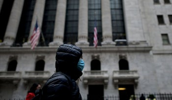 A woman with a facial mask passes the New York Stock Exchange on February 3, 2020.