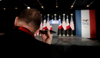 A supporter of t Joe Biden listens to his phone at a rally in Des Moines, Iowa, U.S., February 3, 2020.