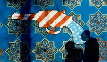 Men walk past a mural on a wall of the former U.S. embassy in central Tehran, January 14, 2008.