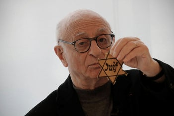 Victor Perahia shows a Jewish badge as he speaks to students during a workshop dedicated to the Holocaust remembrance at the Drancy Shoah memorial, outside Paris, January 30, 2020.