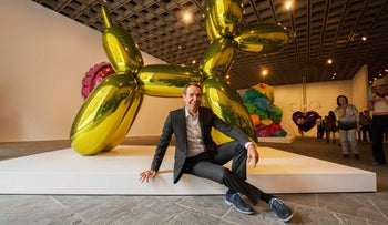 Artist Jeff Koons poses in front of his creation 'Balloon Dog' (Yellow) before the opening of his retrospective at the Whitney Museum of American Art in New York, on June 24, 2014.