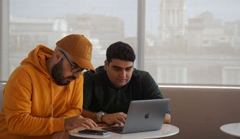 Iranian cybersecurity experts and members of Certfa Nariman Gharib (L) and Amin Sabeti check their messages as they work from their office in London, Britain January 7, 2020.