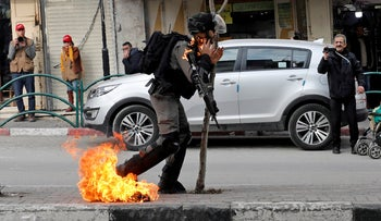 An Israeli border policeman is on fire as he is hit with a molotov cocktail thrown by Palestinian demonstrators during a protest in Hebron, in the West Bank, on February 3, 2020.