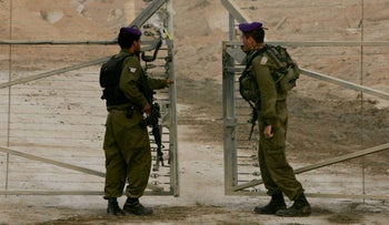 Israeli soldiers close the gate after troops left the Gaza Strip through the Kissufim Crossing into Israel following the settlement pullout early on Monday, September 12, 2005.
