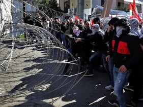 Protesters try to remove barbed wires that block a road leading to the U.S. embassy during a protest against the Trump peace plan in Aukar, east of Beirut, Lebanon, Sunday, Feb. 2, 2020.