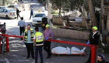 Israeli security and emergency personnel stand next to the body of a suspected assailant in Jerusalem's Old City, February 6,2020.